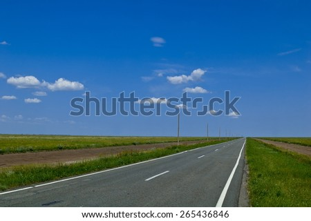 Deserted old asphalt road in a field - stock photo