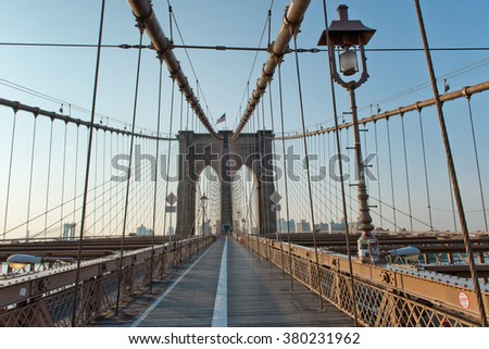 Deserted Pedestrian Walkway Leading Through Arches and Support Cables of Historic Brooklyn Bridge, Iconic Landmark and Tourist Destination in New York City, New York, USA at Sunset