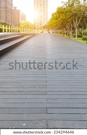 Deserted walkway and bench steps in an urban park surrounded by high-rise commercial buildings , low angle view - stock photo
