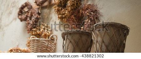 Design and style banner - Rustic garden pots, old wicker baskets and dry plant garlands and wreaths on grunge wall - warm brown and beige color shades background - stock photo