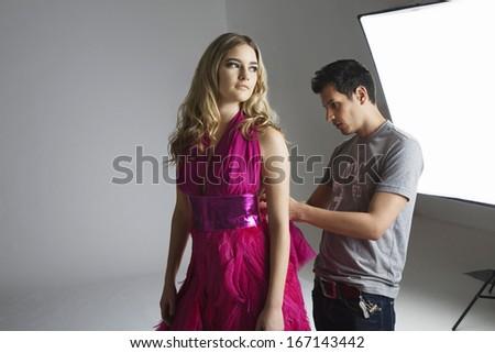 Designer adjusting dress back on fashion model in studio - stock photo