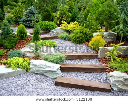 Designer garden with fresh plants and stones - stock photo