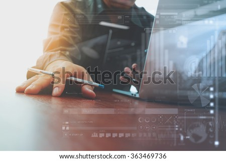 designer hand working and smart phone and laptop and digital business strategy layer effect on wooden desk in office as concept