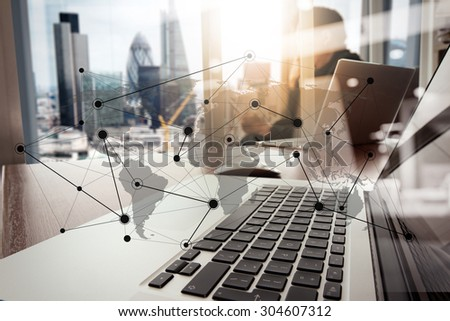 designer hand working and smart phone and laptop on wooden desk in office with london city background with social media diagram - stock photo