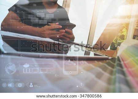 Designer hand working with laptop computer and smart phone and digital tablet with digital design diagram layer on wooden desk as responsive web design concept