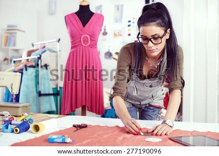 Designer measuring textile material - stock photo
