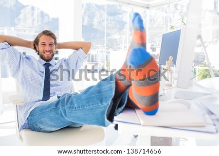 Designer relaxing at desk with no shoes and smiling in bright modern office - stock photo