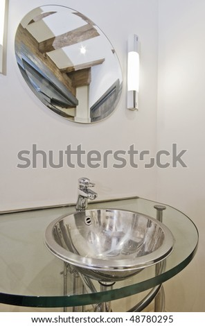 designer stainless steel hand wash basin on a glass shelf
