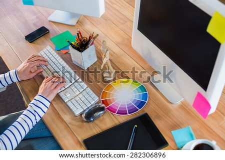 Designer typing on keyboard in the office - stock photo