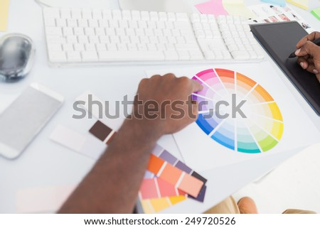 Designer using graphics tablet and colour wheel in the office