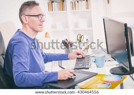 Designer using graphics tablet in the office - stock photo