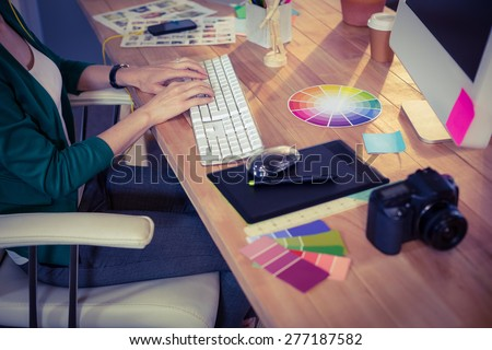 Designer working at her desk in creative office - stock photo