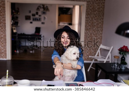 Designer working at home office and holding her puppy in coffee breaks. Selective focus, depth of field, focus at one point - stock photo