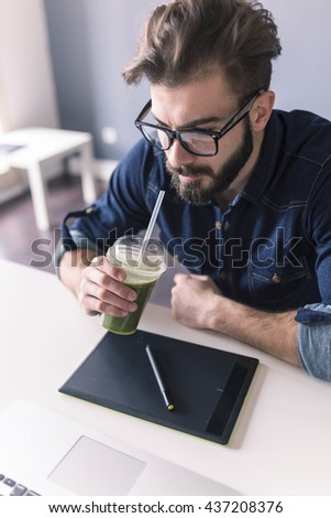 designer working with graphics tablet in the office and drinking healthy smoothie