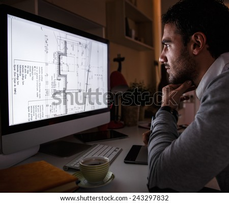 Designer works on new project.He working late into the night. - stock photo