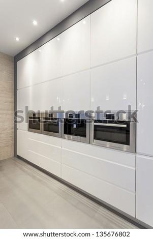 Designers interior - white, minimalistic shelves in kitchen - stock photo