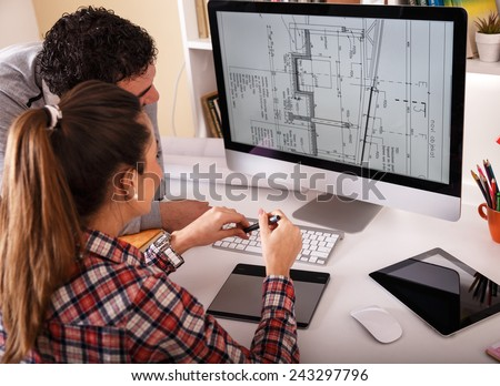 Designers working on new project.They looking in blueprint on screen and discussing.