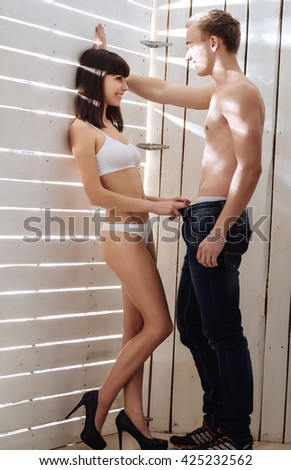 Desire and temptation.Young shirtless man carrying his girlfriend. - stock photo