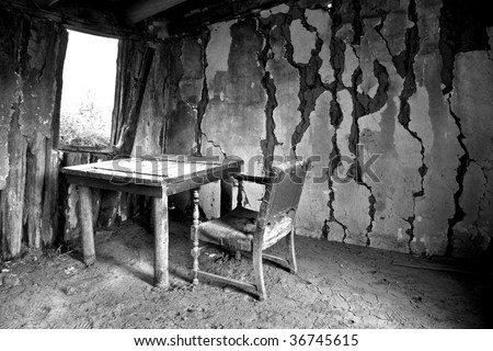 Desk and Chair in an abandoned cabin - stock photo