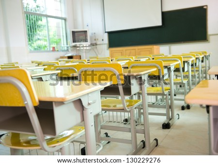 desk and chairs in classroom. - stock photo