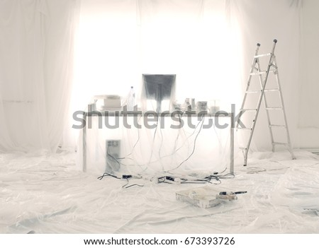 desk and computer covered in transparent dust sheets in preparation for decoration
