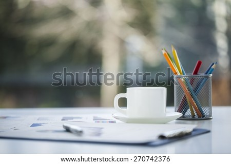 Desk. Close-up image of an office desk at morning with a cup of tea and financial documents - stock photo