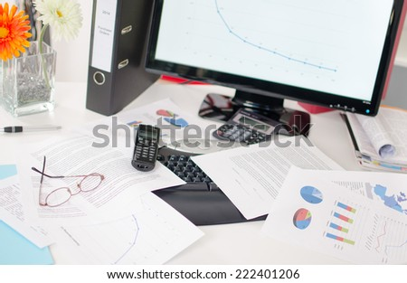Desk cluttered with business documents - stock photo