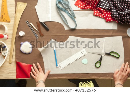 Desk designer fashion. Fashion designer starts cutting fabric to create fashionable clothes. - stock photo