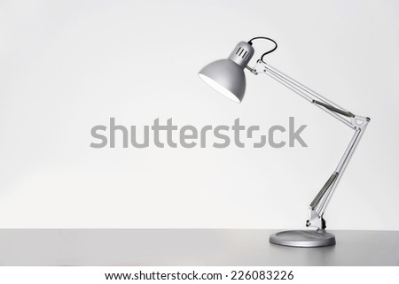 Desk lamp on table over white background - stock photo