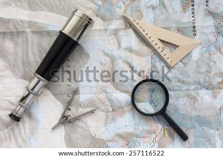 Desk of explorer. Top view of desk covered with the topographic map with typical items of pioneer-navigator: sea telescope, navigational triangle, magnifier and compass - stock photo