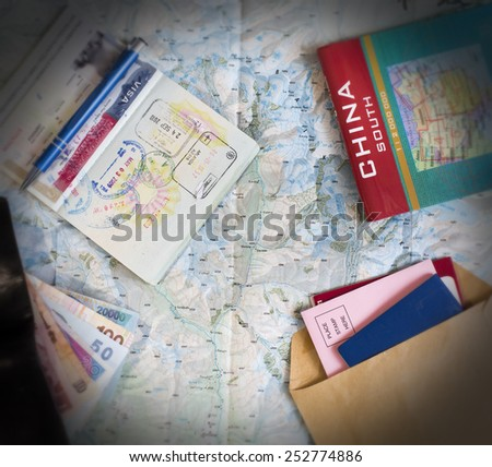 Desk of frequent traveler. The composition of essential items for trip: passport with visa and many stamps, cash notes of different countries, wallet and envelopes, folded map of China and opened map