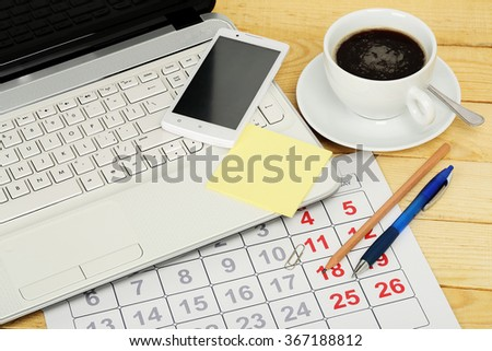 desk with a laptop, calendar and other objects - stock photo
