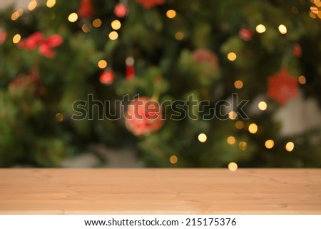 Desk with christmas tree in background at home in the living room - stock photo