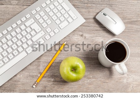desk with keyboard and mouse and green apple - stock photo