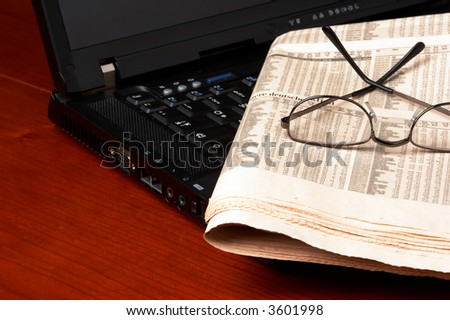 Desk with laptop, newspaper, glasses - stock photo