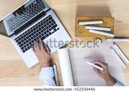 Desk with laptop, pens and scetches roll, elevated view - stock photo