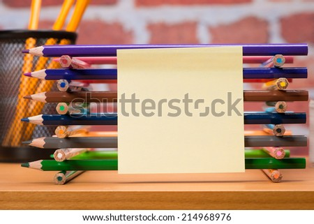 Desk with school supplies and colored pencil in front of brick wall