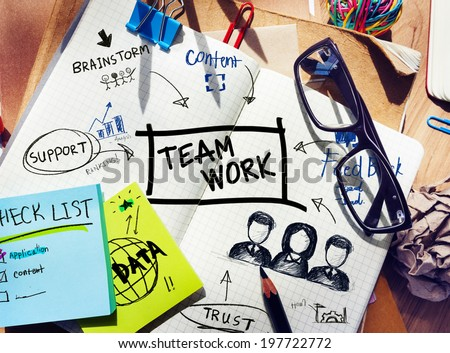 Desk with Tools and a Notebook with Ideas About Teamwork - stock photo