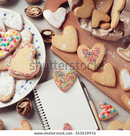 Desk with Valentines cookies with notepad