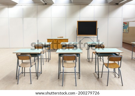 desks and blackboard in classroom at school - stock photo