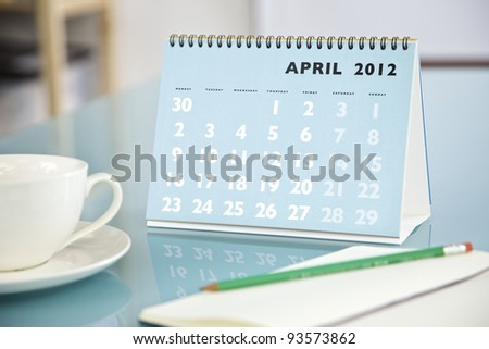 Desktop calendar sitting on a glass desk showing the month of April 2012 - stock photo