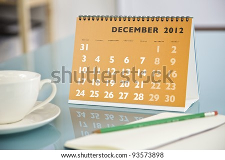 Desktop calendar sitting on a glass desk showing the month of December 2012 - stock photo