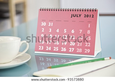 Desktop calendar sitting on a glass desk showing the month of July 2012 - stock photo