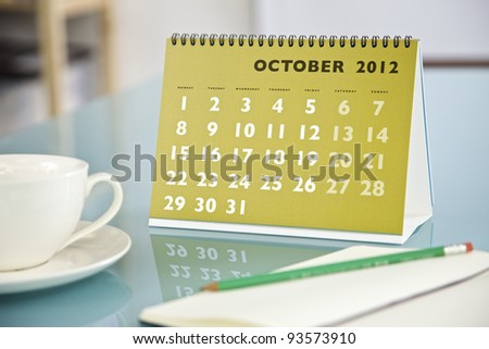 Desktop calendar sitting on a glass desk showing the month of October 2012 - stock photo