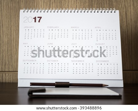 Desktop calendar sitting on desk showing year of 2017. Home office table with stationary, calendar, coffee, paper, pencil, January, Happy New Year, Beginning, Start, Life, office, Home concept.