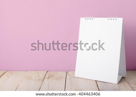 desktop calendars with wooden floor on pink background - stock photo