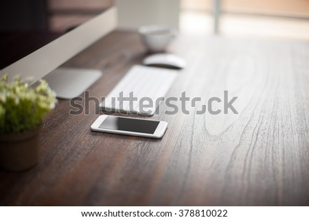 Desktop computer, a smartphone and a small plant sitting on a wooden desk with plenty of copy space and a shallow depth of field - stock photo