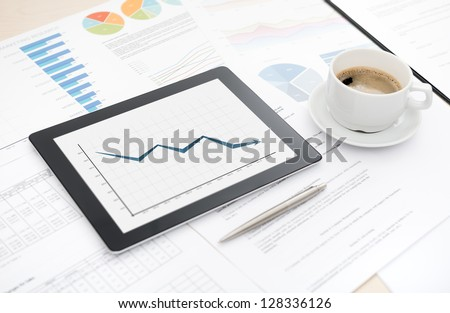Desktop with bad statistic report on a modern digital tablet, some papers with charts and graphs and with cup of coffee. - stock photo