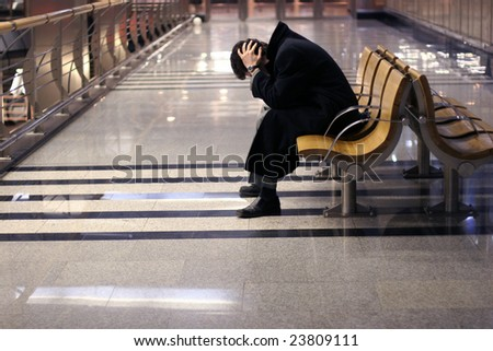 despair businessman sitting on the bench in business center building.
