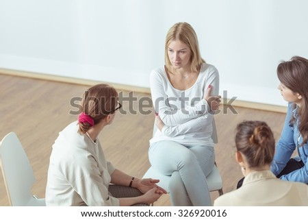 Despair woman talking with coach during therapy - stock photo